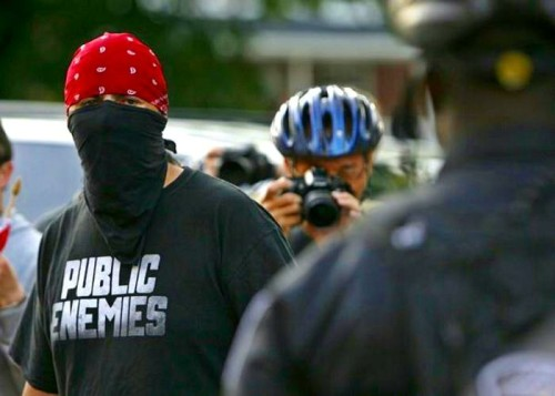 Indigenous activist (in a Public Enemies t-shirt) wears a black mask during a confrontation with police officers at Toronto's G20 protests.