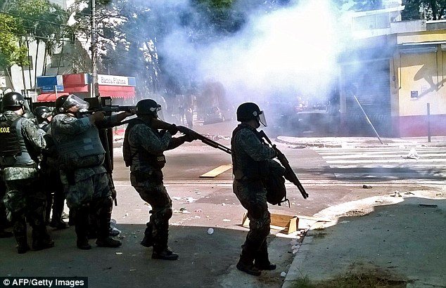Clashes: Riot police fire tear gas during the demonstrations as they to calm the scenes in Brazil