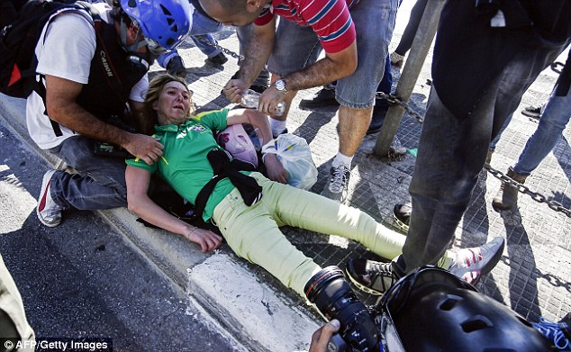 A demonstator receives assistance after being injured during an anti-World Cup protest in Brazil