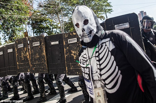 Masked: A protestor stands defiantly in front of the police cordon during the riots near the Arena de Sao Paulo