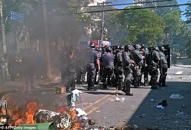 Burn: A fire breaks out on a street during the protests as riot police try and restore calm to Sao Paulo