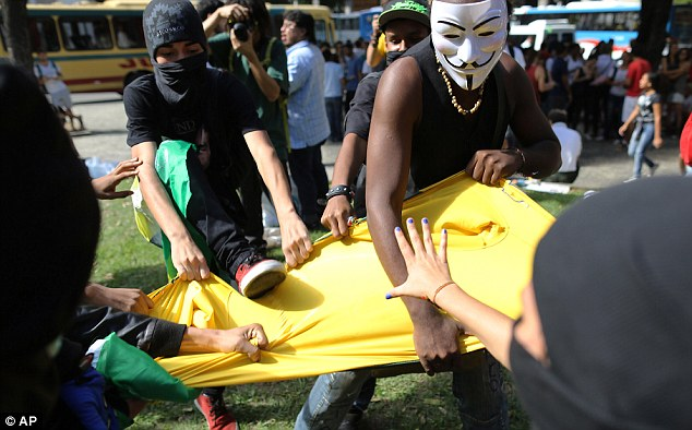 Protesters rip apart a Brazil shirt during their demonstration on the first day of the World Cup in Sao Paulo