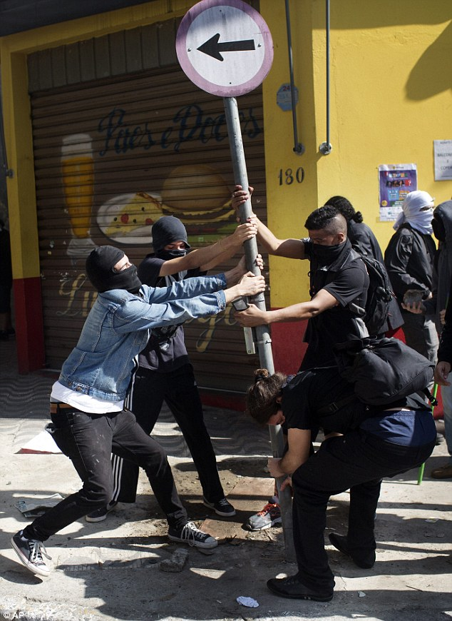 Masked protesters work to uproot a street sign to add to a makeshift barricade during the World Cup protest