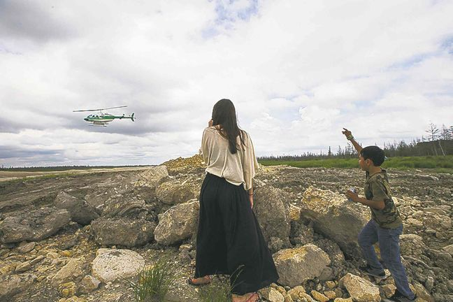 Sienna Gould (left), from Fairford First Nation, and Rio, from Lake St. Martin, watch as the workers leave on a helicopter Saturday.