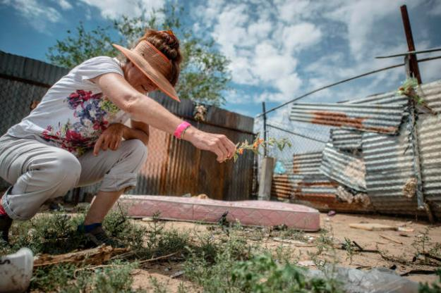 A woman picks wildflowers in the empty lot where two homeless men were attacked in their sleep and beaten to death – so badly they could not be recognized. (Roberto E. Rosales/Albuquerque Journal)