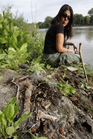 Jo Seenie came in from Roseau River to search for missing women in the Red River Tuesday. She found some bones (foreground) along the shore at the end of Annabella Street. (JOHN WOODS / WINNIPEG FREE PRESS)