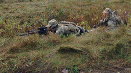 (RCMP tactical unit officers crouch in the grass during Oct. 17, 2013, raid on Mi'kmaq Warrior Society anti-fracking camp. APTN/File)