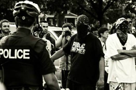 G20, Red Power United, Harrison Friesen (in the Public Enemies T-shirt) engages Toronto police officers. Photo: by Isha Thompson Windspeaker