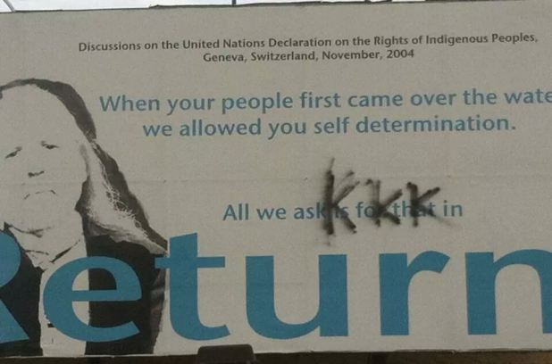 The letters KKK can be seen in black spray paint on a billboard promoting indigenous rights in North Battleford Sask. Officials in the small city are condemning the act of vandalism.