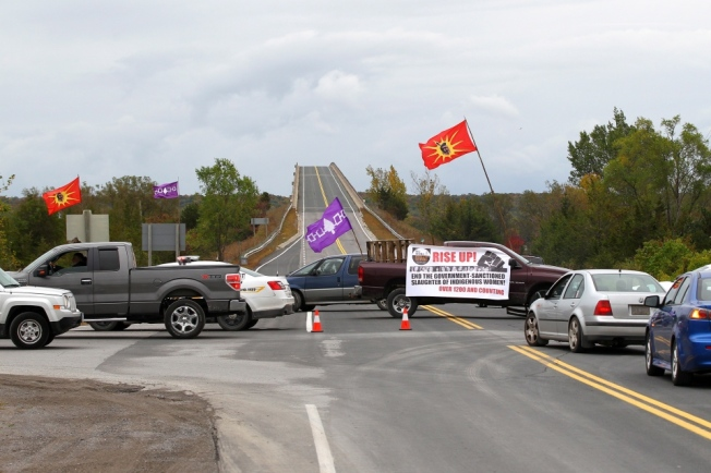 Native flags sit along highway 49, as traffic is being redirected in Tyendinaga, Ont., near Belleville, on Saturday, Oct. 4, 2014. Protesters calling for action on missing and murdered aboriginal women have closed stretches of two highways in Ontario. (Lars Hagberg / The Canadian Press)