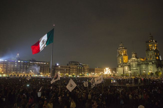 Protesters stand in central square, known as the Zocalo, to protest at the government's response to the mass disappearance of 43 college students in Mexico City, Mexico, on Nov. 20, 2014. Close
