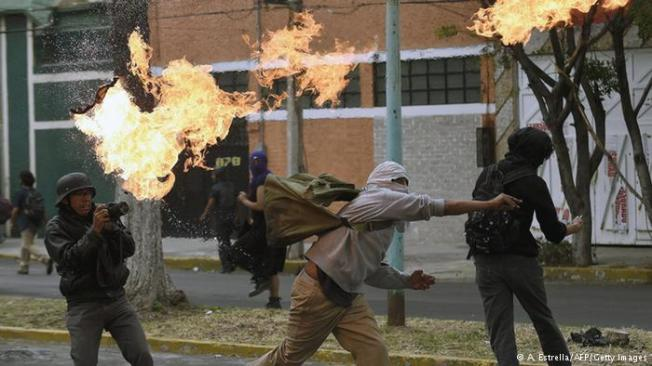 Masked protesters enraged over the suspected massacre of 43 university students clashed with police on the streets of the capital, Mexico City Thursday.