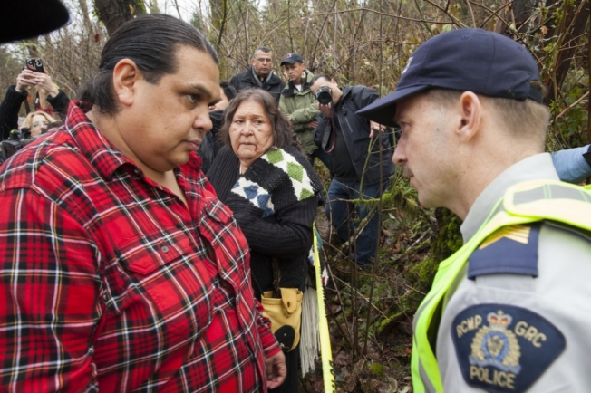 Rueben George speaks with the RCMP at a police line on Burnaby Mountain, as mother Amy George looks on.