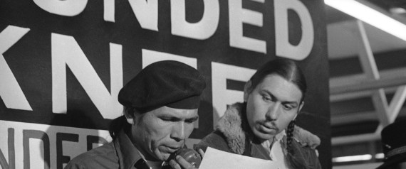 File - In this March 18, 1973 file photo taken in Wounded Knee, S.D., American Indian Movement leader Dennis Banks, left, reads an offer by U.S. government seeking to effect an end to the Native American takeover of Wounded Knee. Looking on is AIM leader Carter Camp. Camp, a longtime activist with the American Indian Movement who was a leader in the Wounded Knee occupation in South Dakota, died Dec. 27, 2013, in White Eagle, Okla. He was 72. (AP Photo/Jim Mone, File)