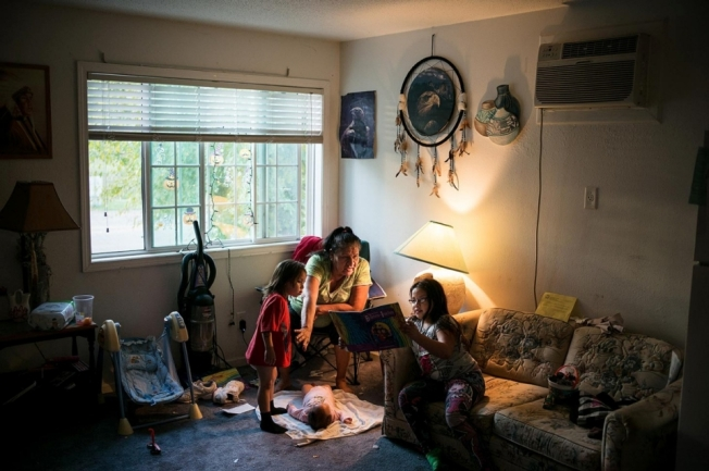 Alexis Tiyona helps her granddaughter Felizcia with her church studies while Nakei, 3, watches with infant Charlie Rue at their home in Sioux Falls, South Dakota on Oct. 21, 2014.Andy Richter for Al Jazeera America