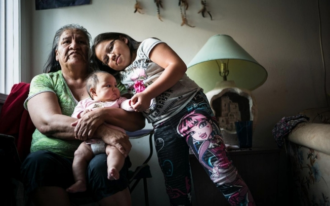 Alexis Tiyona with her grandchildren, three-month-old Charlie Rue and seven-year-old Felizcia, at home in Sioux Falls, South Dakota, on Oct. 21, 2014.Andy Richter for Al Jazeera America