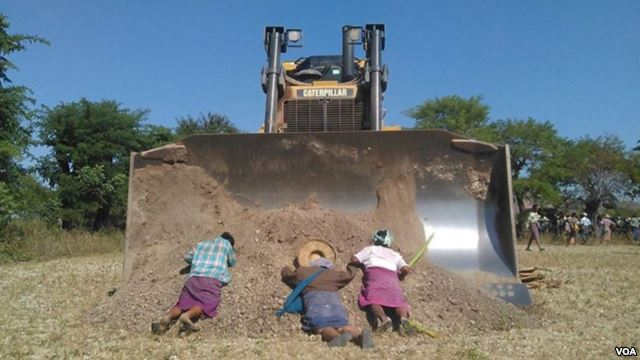 Villagers in northern Myanmar lay in front of a bulldozer as part of their bid to stop the controversial expansion of the Chinese-run Letpadaung copper mine, Dec. 22, 2014. (photographer unknown)