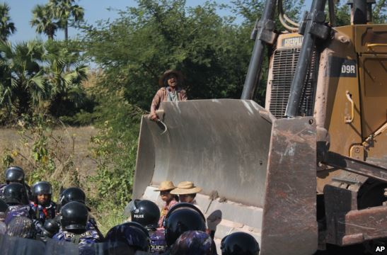 Farmers confront a bulldozer, owned by the Chines mining company, from moving forward as riot police gather at Letpadaung copper mine, Monywa in northwestern Myanmar, Dec. 22, 2014.