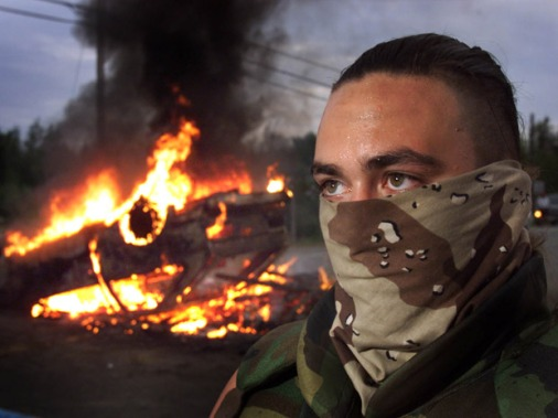 Masked warrior on guard at burning car barricade, Burnt Church, New Brunswick. Source: warriorpublications