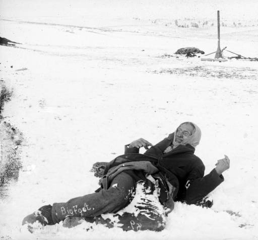 View of the slain body of Chief Big Foot, Native American, Miniconjou Lakota Sioux, propped up in the snow on the Wounded Knee battleground, Pine Ridge Reservation, South Dakota. U. S. soldiers, civilian burial party members, and a stovepipe from an army tent show in background.
