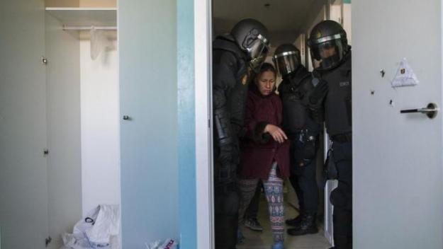 Cecilia Paredes, center, prepares to leave her apartment after riot police broke down the door during the eviction of her and her family in Madrid, Spain, Friday, Jan. 23, 2015.