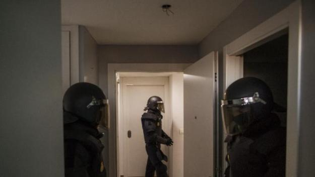 Riot police stand guard as they clear the apartment after they broke down the door during Cecilia Paredes and her family's eviction in Madrid, Spain, Friday, Jan. 23, 2015.