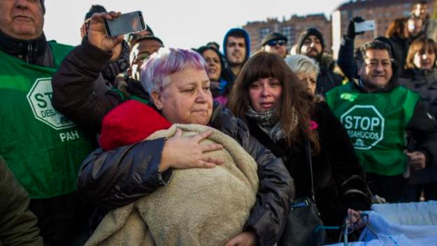 Members of the Victims' Mortgage Platform (PAH) carry Cecilia Paredes's baby, Dilan, a baby born less than two months ago, centre left, after Cecilia and her family got evicted in Madrid, Spain, Friday, Jan. 23, 2015