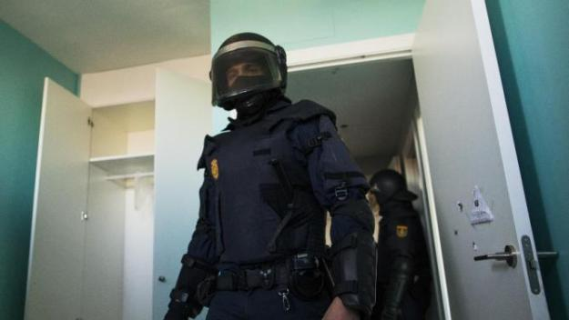 Riot police clear the apartment after they broke down the door during Cecilia Paredes and her family's eviction in Madrid, Spain, Friday, Jan. 23, 2015