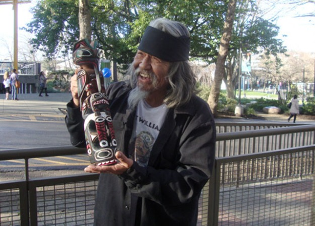 Rick Williams holding a totem pole he hand-carved and painted. Photo by Kayla Schultz.