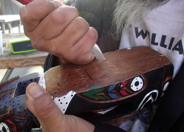 Rick Williams carving his name into a totem pole a customer purchased. Photo by Kayla Schultz.