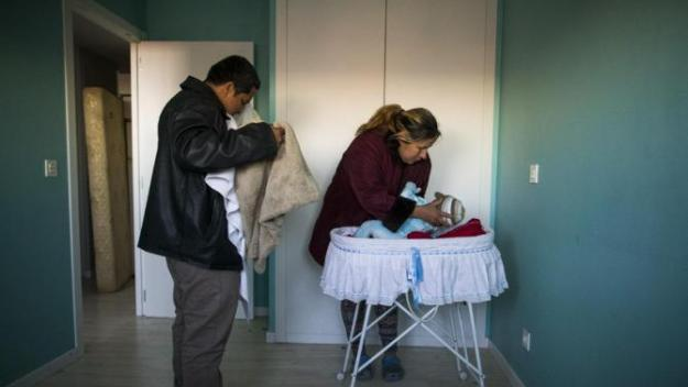 Furniture is stacked behind the main door to stop riot police entering the apartment as Cecilia Paredes and her husband Wilson Ruilova prepare to leave with their baby Dilan during their eviction in Madrid, Spain, Friday, Jan. 23, 2015.