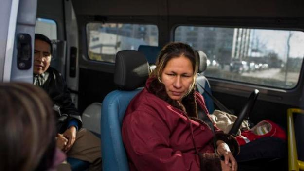 Cecilia Paredes, center, and Wilson Ruilova, 35, left, look at a social worker closing the van as social services take them together with her baby Dilan, right, after they got evicted in Madrid, Spain, Friday, Jan. 23, 2015.