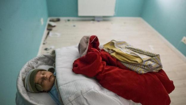 Cecilia Paredes's baby, Dilan, born less than two months ago, sleeps in a room empty of furniture as the family prepares to leave during their eviction in Madrid, Spain, Friday, Jan. 23