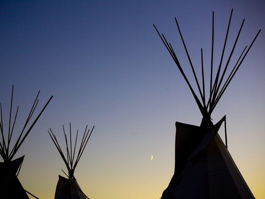 A crescent moon rises between lodges during the Kul Wicasa Pow Wow in Lower Brule, S.D., on Aug. 13, 2010. Between 2007 and 2013, $25 million in aid to the tribe is unaccounted for, according to Human Rights Watch. (Photo: (Sioux Falls, S.D.) Argus Leader)
