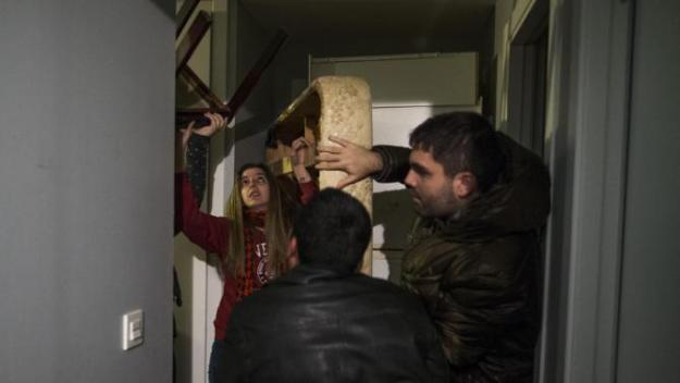 Wilson Ruilova, 35, centre, and members of the Victims' Mortgage Platform (PAH) move furniture to the main door as they try stop his and his family eviction in Madrid, Spain, Friday, Jan. 23, 2015.