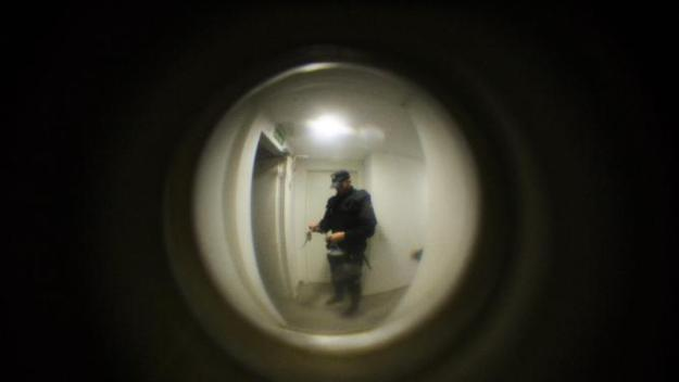 Riot police unblock the building doors as they arrive to evict Cecilia Paredes and her family in Madrid, Spain, Friday, Jan. 23, 2015.