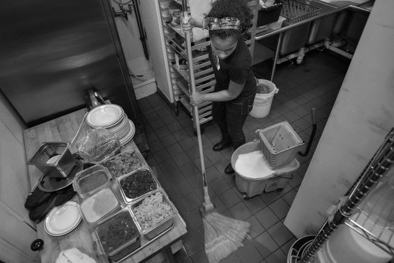 Priestess Bearstops cleans up at the end of her shift at a health food restaurant in Minneapolis