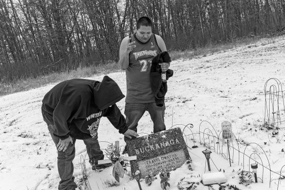 """Dell and Gordy visit the grave of Travis Buckanaga. """"That's how we got to know Senister,'' says Dell. """"Because this guy right here died.''"""