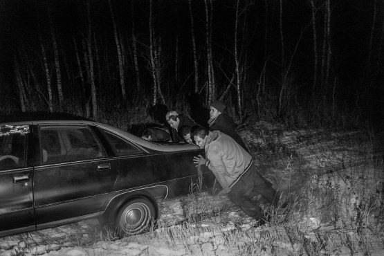 After wrecking their car, the boys try to push it out of a snowy ditch.