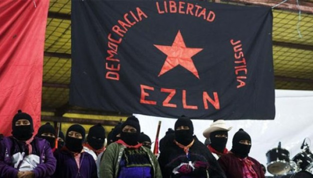 Zapatistas stand under the Zapatista flag during 20th anniversary celebrations of the armed indigenous insurgency in Oventic December 31, 2013. | Photo: Reuters