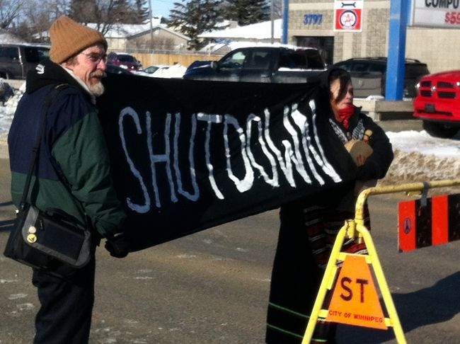 Protestors shut down Portage Avenue westbound at St. Charles Street including Sandy Banman (right) on Friday, Feb. 13, 2015.