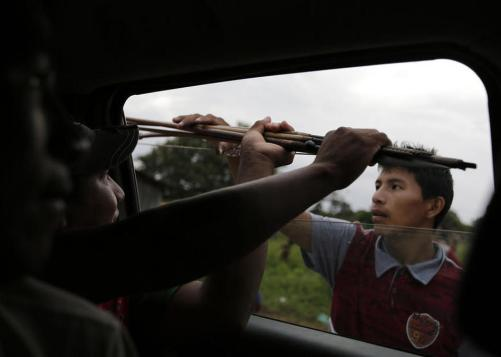 Ka'apor Indians hand bows and arrows to tribal warriors traveling by truck through their village of Ximborenda, on the way to search for and expel loggers from the Alto Turiacu Indian territory, Brazil.