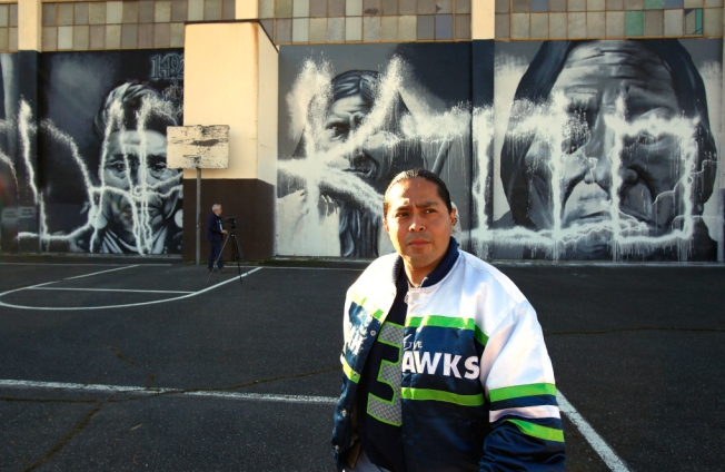 """Andrew Morrison is shown Monday with his murals at the Wilson-Pacific school campus in North Seattle. The letters """"DAPKILO"""" were painted over the faces of Chief Joseph, Geronimo and Sitting Bull. """"He was stupid enough to write his own name,"""" Morrison said of the vandal. (Mark Harrison/The Seattle Times) Less"""