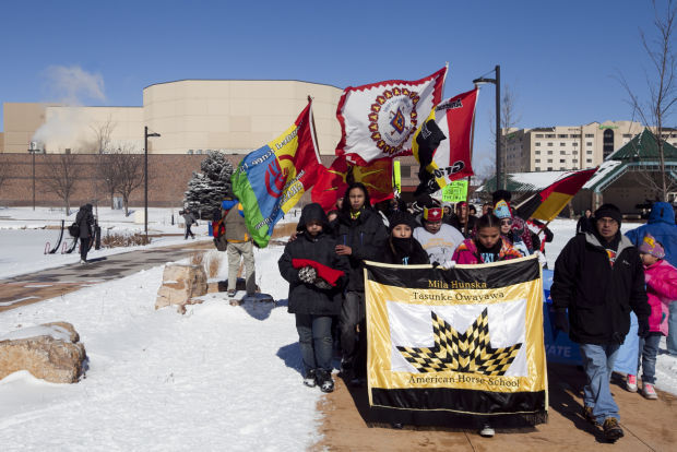 Native Lives Matter movement supporters walk past the Rushmore Plaza Civic Center Thursday afternoon en route to the City/School Administration Center as part of the All Relations Community March Against Racism.