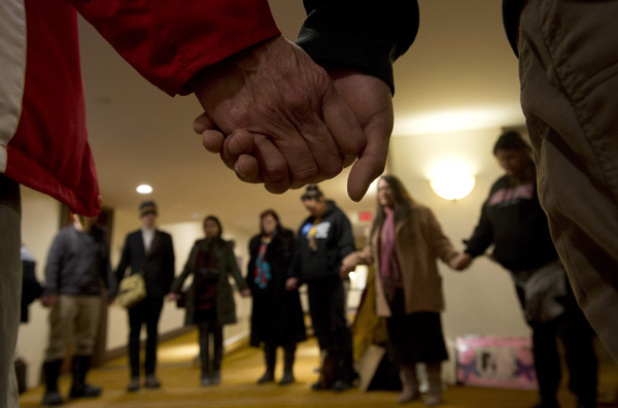 A group of aboriginal protesters hold hands during a prayer outside the National Roundtable on Missing and Murdered Indigenous Women and Girls Friday, February 27, 2015 in Ottawa. The Canadian Press
