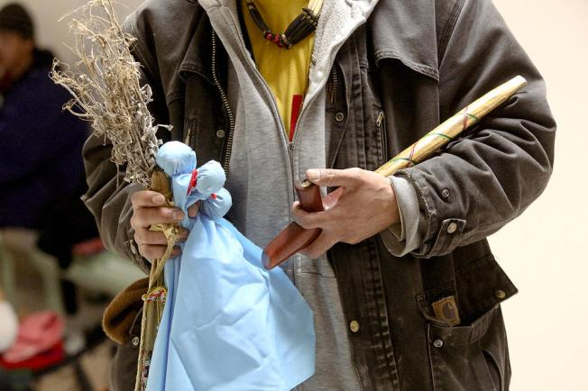 Iyawbance LaPrairie, the son of Mushkoob Aubid, holds sage, tobacco ties, and a traditional pipe with tobacco during a gathering at the University of Minnesota Duluth on Sunday. (Clint Austin / caustin@duluthnews.com)