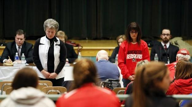 Two attendees turn their backs to the board as board members speak during the Lancaster School Board vote that retired the Redskins mascot and nickname in Lancaster, N.Y., Monday, March 16, 2015. (AP Photo/Jen Fuller)
