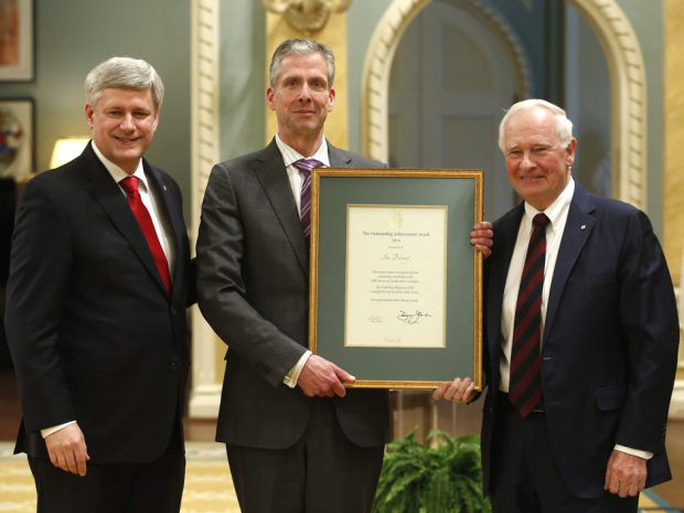 Prime Minister Stephen Harper, left, and Governor General David Johnston, right, present the Outstanding Achievement Award to Ian Burney, assistant deputy minister of trade and negotiations in the Department of Foreign Affairs, at a ceremony at Rideau Hall in Ottawa, Friday, February 27, 2015. THE CANADIAN PRESS/ Patrick Doyle