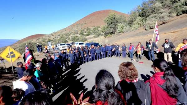 Police and protesters share a prayer near the visitors station on Mauna Kea.
