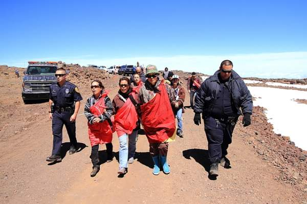 "Shouts of ""ku kiai mauna"" — the guardians of the mountain — reverberated off ancient cinder cones and dome-shaped telescopes Thursday at Mauna Kea's summit as police led 12 arrested protesters away from the Thirty Meter Telescope construction site. Photos courtesy Ehitu/Keeling/Special to West Hawaii Today"